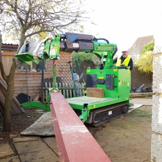The Hooka on hire carrying a steel I-beam to the rear of a property using a dolly instead of a conventional crane hire. Hired from Hook-up Solutions call 07971 174 523 for Southern Hire or 01462 499 642 for Eastern Hire