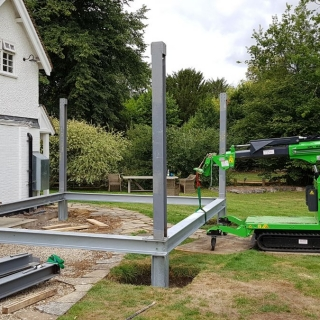 The Hooka lifting and moving a steel I-beam with precision on site with restricted access